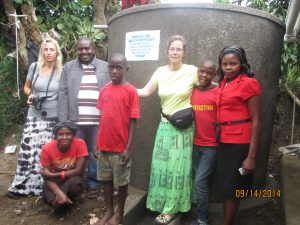 Evas poses with Dr. Shannon and one of the childrens' sponsors Keri at one of Mosaic families after Mosaic donated a water tank to the same family.